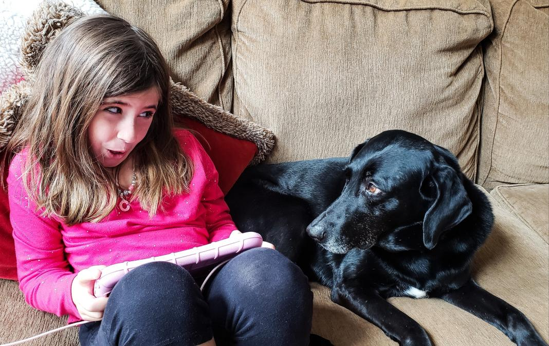 Little girl talking to the dog who is wondering what language she speaks and getting a little